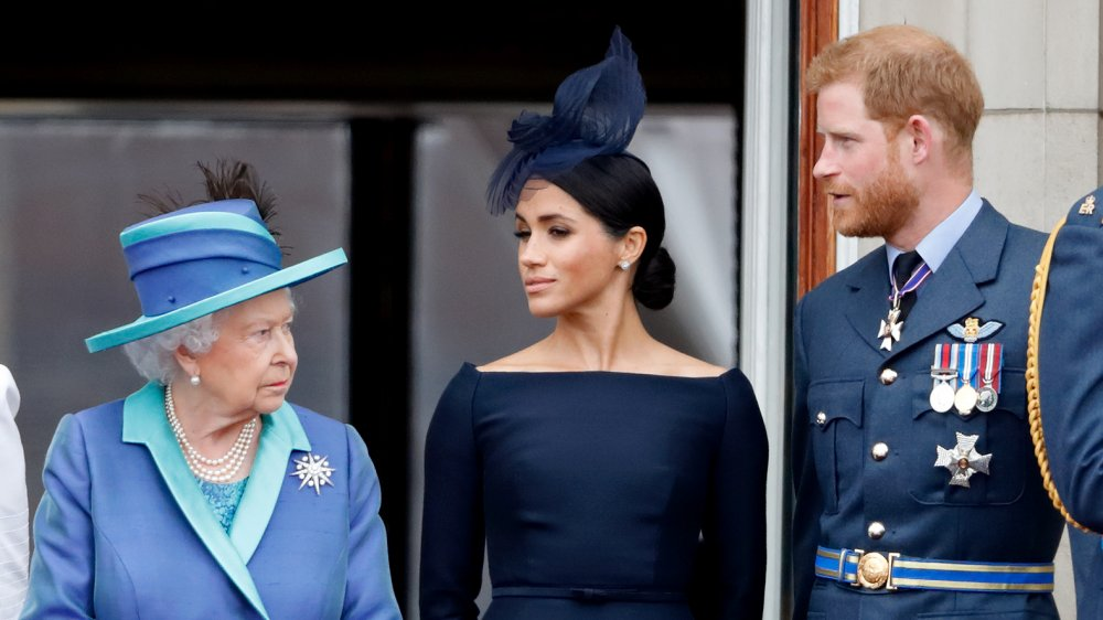 Drottning Elizabeth, Meghan Markle och prins Harry atch en förbiflygning för att markera hundraårsjubileet av Royal Air Force från balkongen i Buckingham Palace 2018
