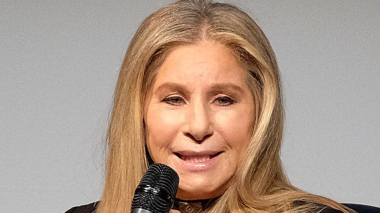 Barbra Streisand med mikrofon i handen, talande