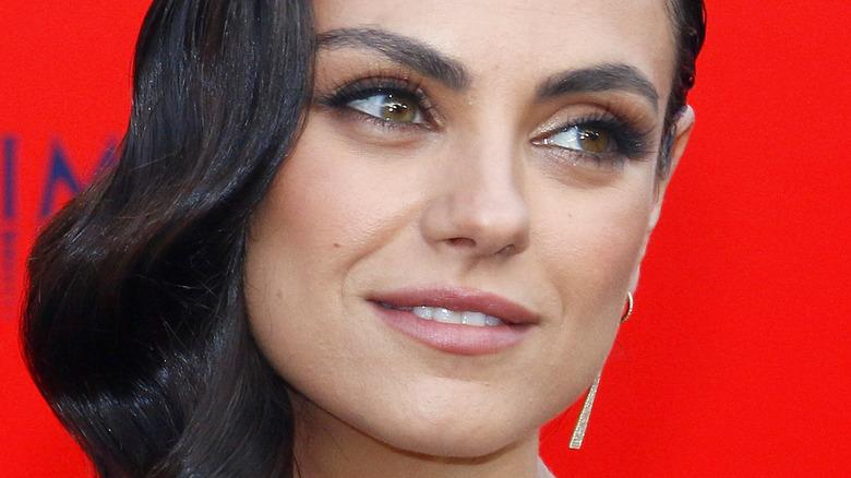 Mila Kunis med röd bakgrund